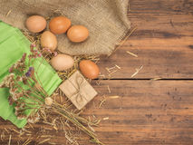 Rural creative background with brown eggs, burlap, straw, green paper and dry flowers on wooden table from old planks Royalty Free Stock Images
