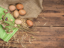 Rural creative background with brown eggs, burlap, straw, green paper and dry flowers on wooden table from old planks stock photo