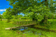 Rural Crossings. Depicts a small wooden bridge crossing over a body of water Stock Photography