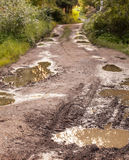 Rural damaged road with muds Royalty Free Stock Photo