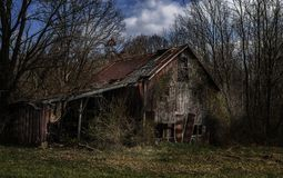Rural decay setting in a a old barn. A old, rustic, decaying barn in late afternoon in a rural area surrounded by trees royalty free stock photography
