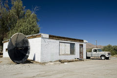 Rural Desert Building. A rural deserted shop in a small desert town, complete with custom painted satellite dish and transportation royalty free stock photos