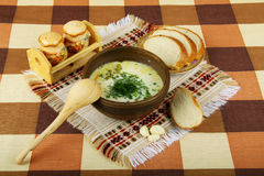 Rural dinner with soup, bread and garlic. Served in wooden dishware Royalty Free Stock Photo