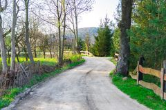 Rural dirt road, beautiful village in the summer, the road under the old fallen fence royalty free stock images
