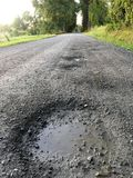 Rural Dirt Road Potholes. A rural image from Vermont of a country dirt road with a closeup on the potholes wet with recent rain Royalty Free Stock Image