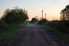 Rural dirt road at sunset in fog Stock Photo