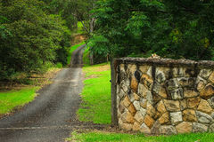 Rural driveway entrance with sandstone wall. Winding country road driveway entrance with sandstone brick wall surrounded by trees Royalty Free Stock Image