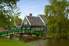 Rural dutch scenery of small old houses and canal in Zaanse, Net Royalty Free Stock Image