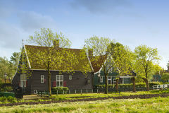 Rural dutch scenery of small old houses and canal in Zaanse, Net Royalty Free Stock Photo