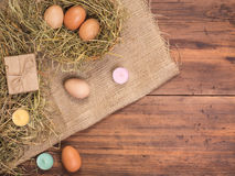Rural eco background with brown chicken eggs, colored candles, gift box and straw on the background of old wooden planks Royalty Free Stock Image