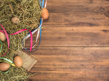 Rural eco background with brown chicken eggs, colored ribbons and straw on the background of old wooden planks. The view Royalty Free Stock Photo