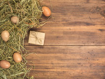 Rural eco background with brown chicken eggs, gift box and straw on the background of old wooden planks. The view from Stock Image