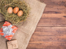 Rural eco background with brown chicken eggs, gift box and straw on the background of old wooden planks. The view from Stock Images