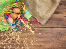 Rural eco background with brown chicken eggs, a piece of burlap, colored ribbons and straw on the background of old Stock Photos