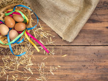 Rural eco background with brown chicken eggs, a piece of burlap, colored ribbons and straw on the background of old Stock Images