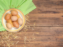 Rural eco background with brown chicken eggs, a piece of burlap and straw on the background of old wooden planks. The Stock Photo