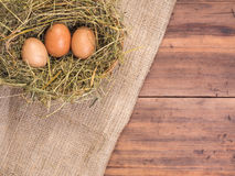 Rural eco background with brown chicken eggs, a piece of burlap and straw on the background of old wooden planks. The Royalty Free Stock Photography