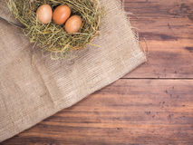 Rural eco background with brown chicken eggs, a piece of burlap and straw on the background of old wooden planks. The Royalty Free Stock Photos