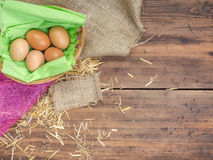 Rural eco background with brown chicken eggs, a piece of burlap and straw on the background of old wooden planks. The stock images