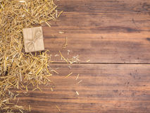 Rural eco background with gift box and straw on the background of old wooden planks. The view from the top. Creative stock images