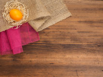 Rural eco background with orange chicken egg and straw on the background of burlap and old wooden planks. The view from Royalty Free Stock Images