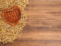 Rural eco background. Wicker-work basket from withe in heart shape with straw on the background of old wooden planks Royalty Free Stock Photos