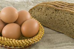 Rural eggs lying in a basket near bread. Many fresh rural eggs lying in a wattled small basket near to fresh bread on a cloth from a rough fabric Royalty Free Stock Image
