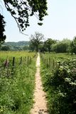 Rural English path. Footpath running between fields and meadows in Rural England Stock Photos