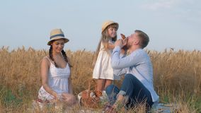 Rural family portrait, little happy kid girl eats yummy sweet bun and treats her parents at village picnic in reaped stock footage