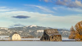 Old farmhouse with a wooden weathered barn in winter with mountains royalty free stock photography