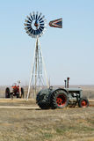 Rural Farm Scene. Two tractors stand near a windmill in rural Colorado Royalty Free Stock Photo