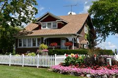 Rural Farmhouse. This is a Summer picture of a rural farmhouse located in South Barrington, Illinois.  The picture features a white picket fence and flower Royalty Free Stock Photo