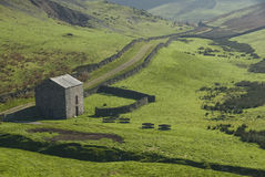 Rural farming stone barn in highland field. Stock Photography