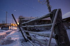 Rural fence covered with brilliant hoarfrost in the winter starlit night.  Stock Images