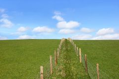 Rural Fencing. Double wooden post and wire fence line dividing a field. Set against a blue sky with alto cumulus clouds Stock Photo