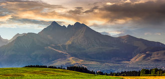 Rural field in Tatra mountains. Panorama of Tatra mountains in evening haze behind the forest and rural field Stock Photo