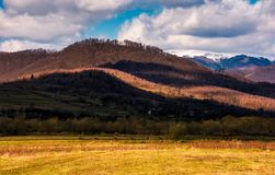 Rural fields at the foot of the mountain. Rural fields at the foot of the forested mountain with snowy top. lovely countryside springtime scenery on a cloudy day Royalty Free Stock Image
