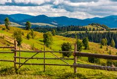 Rural fields on hills in mountainous area. Rural fields behind the wooden fence on hills in mountainous area. lovely countryside landscape in autumn Royalty Free Stock Images