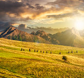 Rural fields near the high mountains at sunset Stock Photography