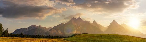 Rural fields near Tatra Mountains at susnet. Rural fields near Tatra Mountains in summer at sunset. beautiful panorama of agricultural area. gorgeous mountain Royalty Free Stock Images