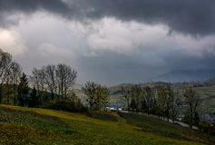 Rural fields on serpentine in bad weather. Mountainous countryside with trees in autumn stormy evening Stock Image
