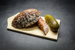 Rural food. Country sausage, slice of bread, cucumber, stacked on a wooden board Stock Photos