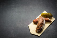 Rural food. Country sausage, slice of bread, cucumber, stacked on a wooden board Stock Photography