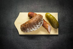Rural food. Country sausage, slice of bread, cucumber, stacked on a wooden board Stock Images