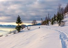 Rural footpath through snowy hillside. Beautiful scenery of mountainous countryside in winter Royalty Free Stock Photography