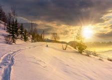 Rural footpath through snowy hillside at sunset Royalty Free Stock Photos