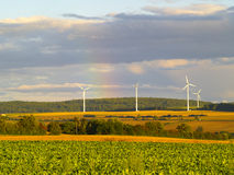 Rural germany. Rainbow over agricultural landscape with wind energy plants in germany, evening light Royalty Free Stock Image