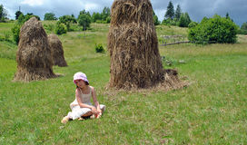 Rural  girl. Girl sits around stack network on meadow Royalty Free Stock Image
