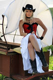 The rural girl. Sexy woman in red corset and a long white skirt sitting in the cart Royalty Free Stock Photography