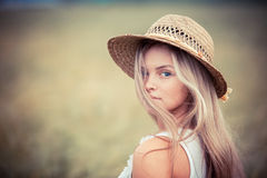 Rural girl in a straw hat. Portrait of the rural girl in a straw hat royalty free stock photos